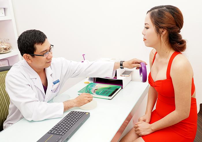 Bác sĩ sử dụng máy quét cầm tay thăm khám cho khách hàng.